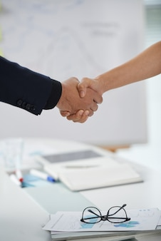 Unrecognizable man and woman shaking hands at meeting start