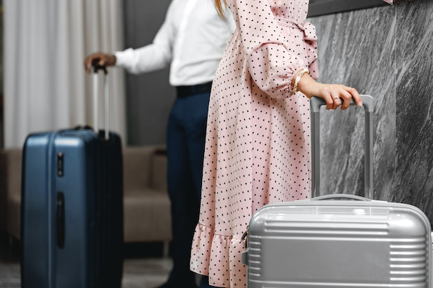 Unrecognizable man and woman with suitcases standing near reception in hotel close up
