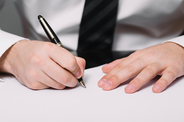 Unrecognizable man writing in office