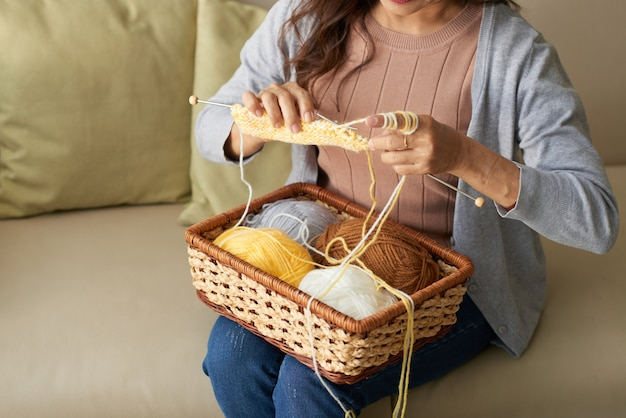 Unrecognizable mature woman knitting scarf sitting on sofa at home