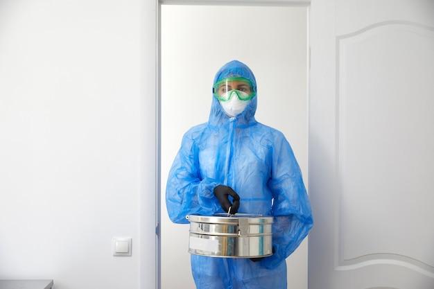 保護用の制服を着た認識できない医学者がドアを開け、サンプルの入った金属ケースを持って実験室に入る。