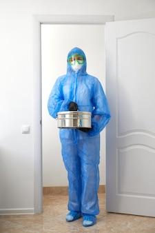 保護用の制服を着てドアを開け、実験室に入る認識できない医学者