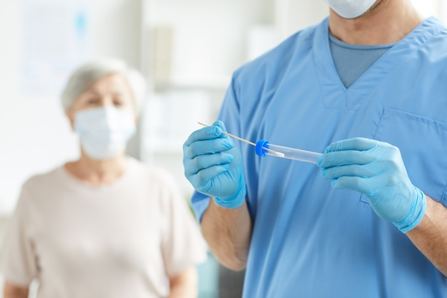 Unrecognizable medical specialist wearing blue uniform holding test tube and swab sample and his patient sitting behind him