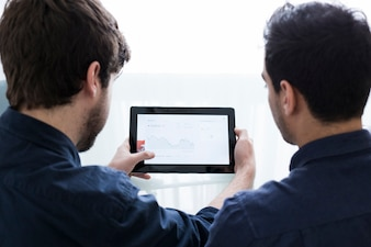 Unrecognizable men looking at graph on tablet