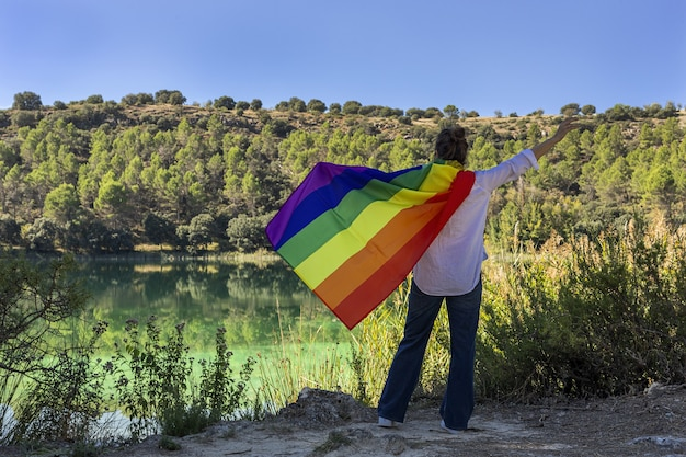 야외 호수에서 게이 무지개 깃발을 들고 알아볼 수 없는 중년 레즈비언 여성. 자유 개념