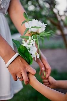 인식 할 수없는 엄마와 딸 꽃 봄 정원에서 손을 잡고 행복 한 여자와 아이, 야외에서 흰 드레스를 입고, 봄 시즌이오고있다. 어머니의 날 휴가 개념