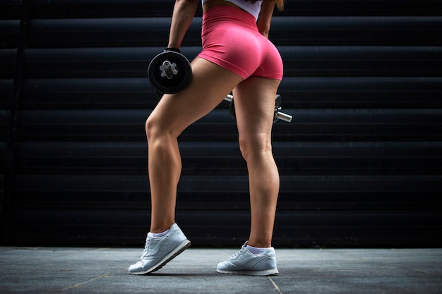 An unrecognizable muscular sportswoman athlete with strong legs posing in gym against black background