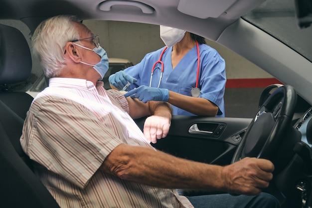 Unrecognizable nurse inoculating senior driver in car