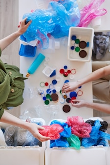 Unrecognizable people sorting plastic waste at home before recycling