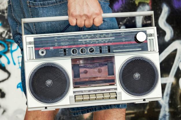 Unrecognizable person carrying a vintage cassette boombox