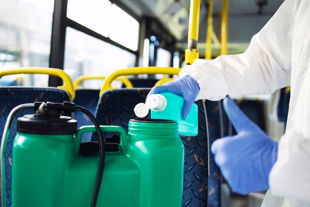 코로나 바이러스에 대한 소독을 시작하기 위해 탱크 저장소에 소독제를 추가 한 장갑이 달린 흰색 보호 복을 입은 인식 할 수없는 사람 클리너.