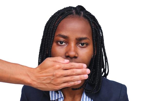 До неузнаваемости человек закрывает рот серьезной афро-американской женщины на белом фоне.
