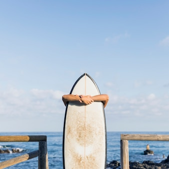 Unrecognizable person embracing surfboard near sea
