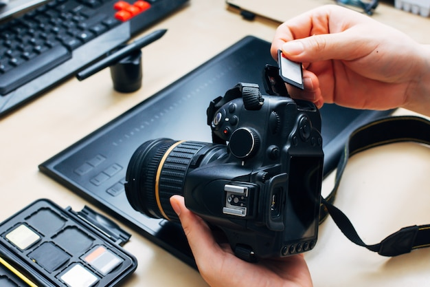 Unrecognizable person holding a camera and insert a memory card into it in his workplace