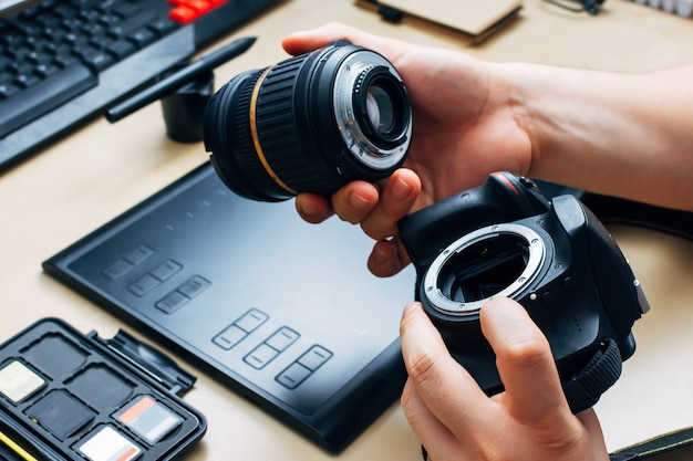 Unrecognizable person holding a camera and puts the lens in his workplace