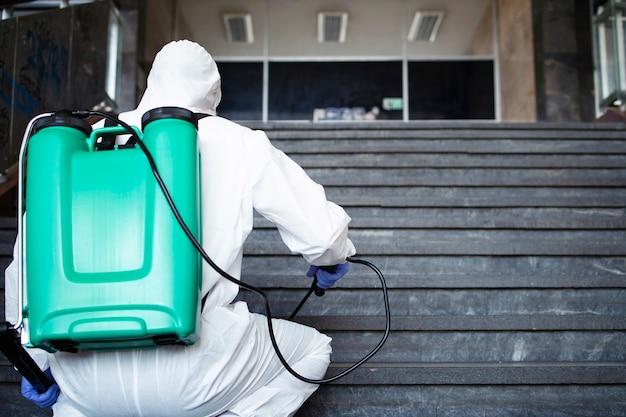 白い化学防護服を着た認識できない人物が、公共の廊下を消毒し、伝染性の高いコロナウイルスの拡散を阻止するための措置を講じています。