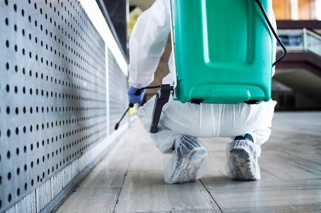 白い保護服を着た認識できない人物が、公共エリアを消毒して、伝染性の高いコロナウイルスの拡散を阻止します。