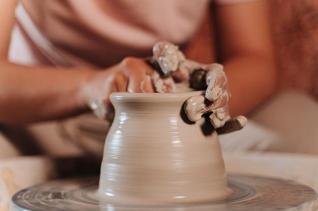 인식 할 수없는 사람이 테라코타라는 재료를 형성하고 있습니다.