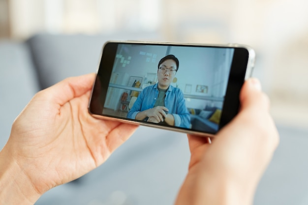 スマートフォンを使用してオンラインビデオ会議に参加している認識できない人、水平クローズアップショット