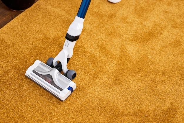 До неузнаваемости человек, использующий пылесос дома, крупным планом. делать уборку дома пылесосом, нанося его на желтый ковер