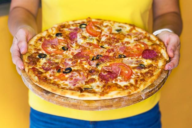 認識できない人、チーズ、タモト、ハム、ソーセージ、オリーブと手でおいしいピザを保持している女性。ペパロニピザの写真を閉じます。レストランでピザを提供するウェイター。国立イタリア料理