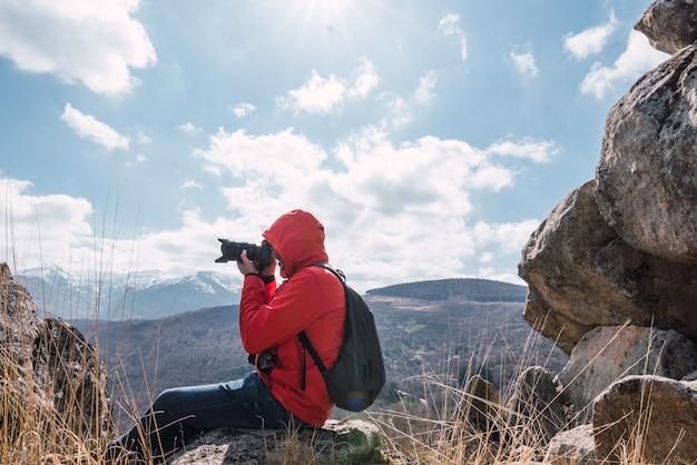 Неузнаваемый фотограф сидит и фотографирует пейзаж с горами
