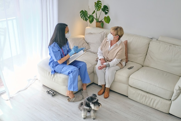 Unrecognizable physician talking to patient in mask against dog indoors