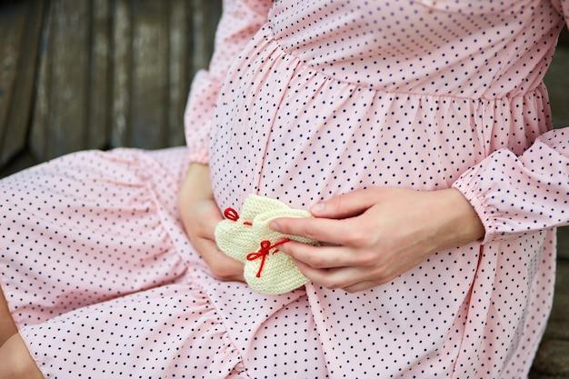 До неузнаваемости беременная женщина трогает живот и держит детскую обувь