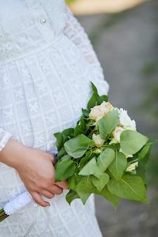 До неузнаваемости беременная женщина трогает живот, держа букет