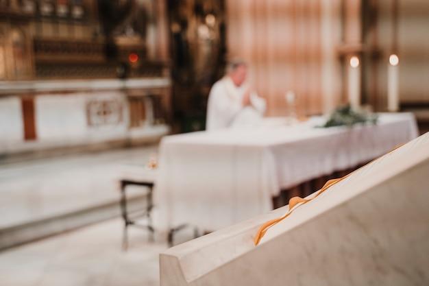 結婚式の結婚式のミサの間に認識できない司祭。宗教概念。セレクティブフォーカス
