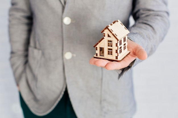 Unrecognizable realtor holding house figurine