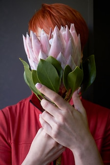 Unrecognizable red-haired female hands holding a pink protea flower in front of face