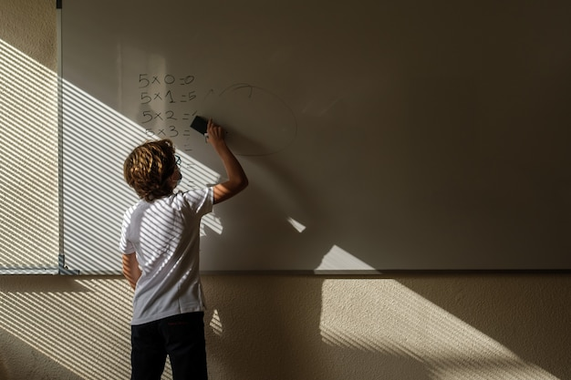 Unrecognizable schoolchild erasing math example from whiteboard during lesson