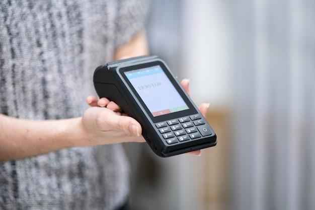Unrecognizable shop assistant using a credit card terminal