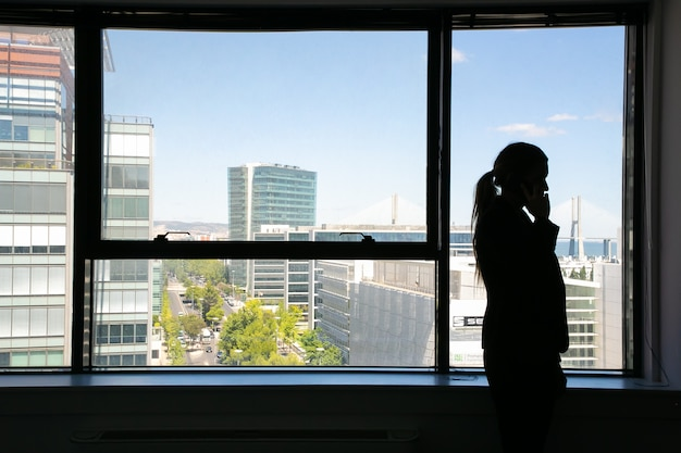 窓際に立って携帯電話で話している実業家の認識できないシルエット。影と街並みのプロのマネージャー。ビジネス、コミュニケーション、会社のコンセプト