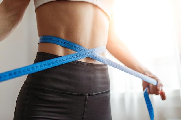 ダイエット中や自宅での運動中に、認識できないスリムな女性の巻尺が腰の周りを測定します