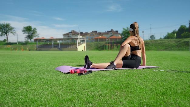 晴れた夏の日にスポーツウェアのトレーニングを着ている認識できないスリムな女の子。スタジアムで走った後、紫色のマットの上で体を伸ばしている若い女性の側面図。柔軟性、ストレッチのコンセプト。