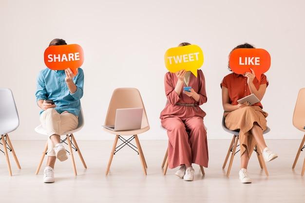 인식 할 수없는 소셜 미디어 사용자가 가젯을 나란히 놓고 트윗, 좋아요 및 공유 비문이있는 다채로운 태그 뒤에 얼굴을 숨 깁니다.
