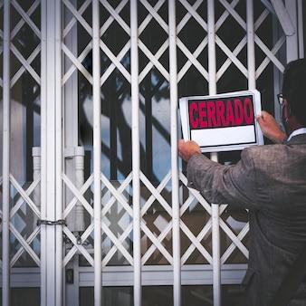 Неузнаваемый владелец магазина кладет закрытый знак на дверь