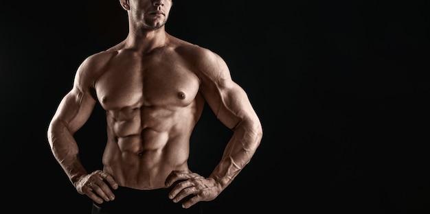 До неузнаваемости сильный спортивный сексуальный мускулистый мужчина на черном пространстве