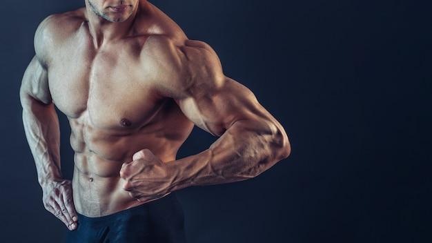 인식 할 수없는 강한 운동 섹시한 근육질 남자 poising, 검은 공간에 팔뚝과 삼각근을 보여주는