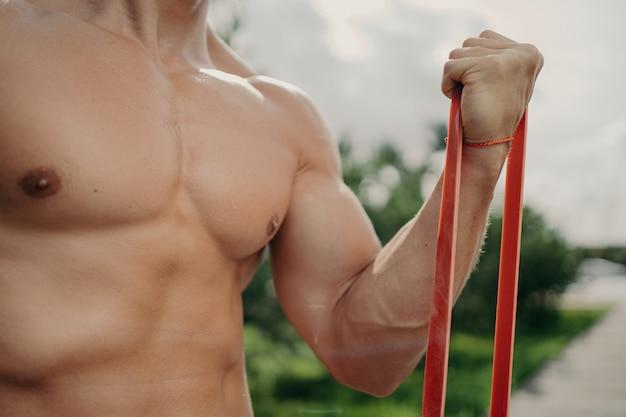 Неузнаваемый сильный мужчина на тренировке с эспандером становится сильнее с каждым днем