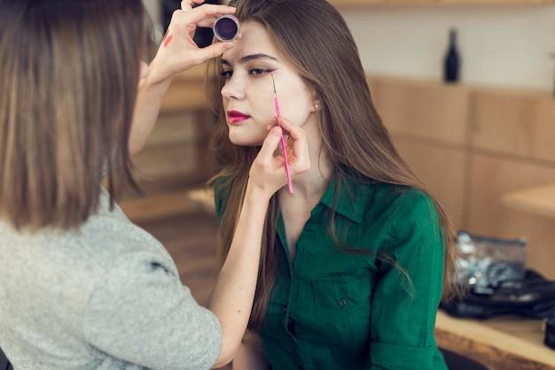 Unrecognizable stylist using eyeliner on model