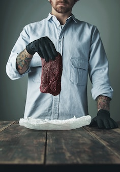 Unrecognizable tattoed butcher in black gloves holds piece of luxury whale meat above white craft paper