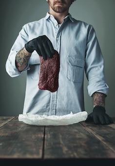 검은 장갑을 입은 인식 할 수없는 문신을 한 정육점이 하얀 공예 종이 위에 고급 고래 고기 조각을 들고 있습니다.