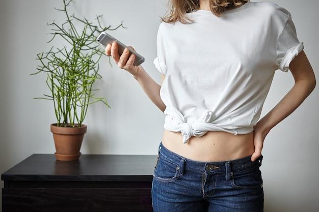 植木鉢と居心地の良い部屋のインテリアでポーズをとってカジュアルなtシャツとジーンズの認識できない10代の少女