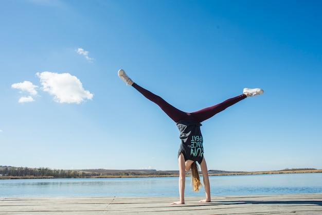 Unrecognizable teenager doing handstand on pier
