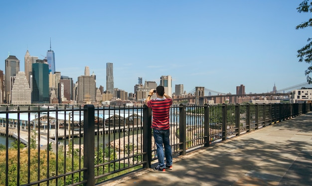Unrecognizable tourist man in brooklyn bay taking photos with his smartphone of manhattan skyline, in new york city