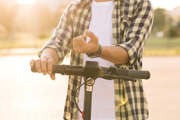 알아볼 수 없는 관광 남자는 공유 주차장, 스마트 시계 응용 프로그램에서 전기 킥 스쿠터 또는 자전거 자전거를 가져갑니다. 에코 교통. 스쿠터용 smartwatch 전화 앱