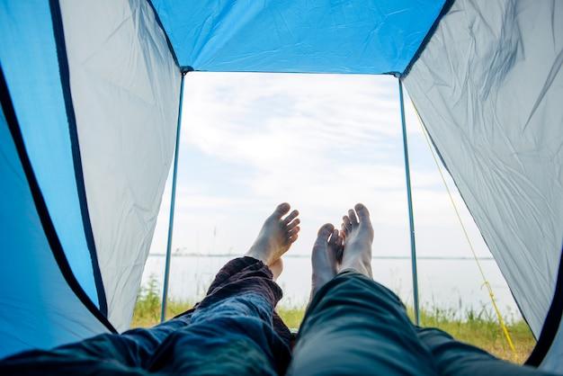 알아볼 수 없는 관광객 부부는 푸른 텐트 안에 누워 아름다운 강 풍경을 관찰합니다. 가족 휴가. 맨발로 건너는 연인들의 텐트 내부에서 본 모습. 여행 및 하이킹 개념입니다.